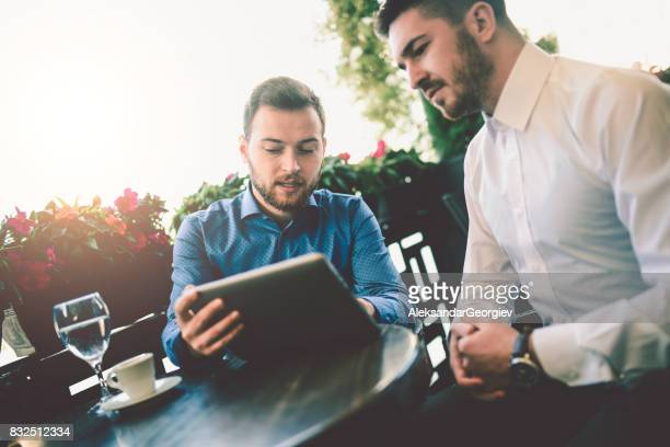 Business Colleagues using Digital Tablet in a Cafe Restaurant