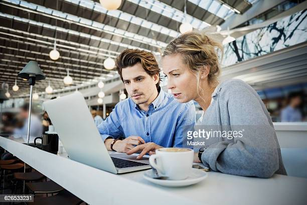 Business colleagues using laptop at airport cafe