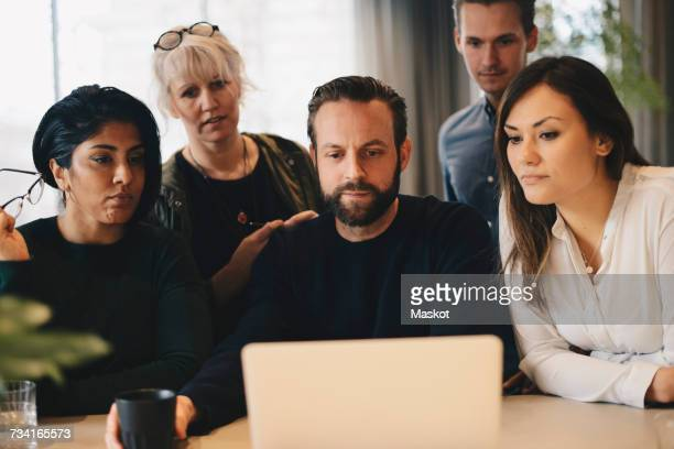 Business colleagues using laptop at conference table together in board room
