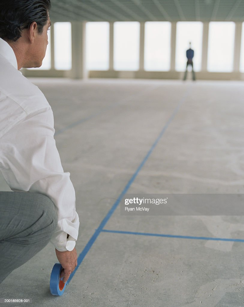 Business colleagues using tape to layout empty office space, rear view : Stock Photo