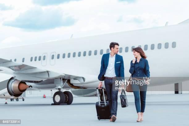 Collega's van het bedrijf lopen op tramac voor het vliegtuig.