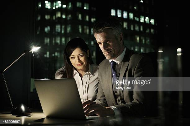 Business colleagues working late in office on laptop