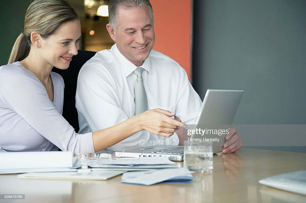 Business colleagues working on laptop computer together : Stock Photo