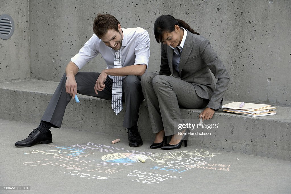 Business colleauges looking at writings on sidewalk : Stock Photo