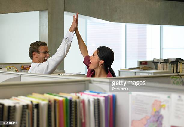 Business collegues high fiving in office cubicles