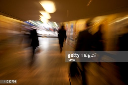 Business commuters walking through corridor : Stock Photo