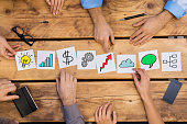 Businesspeople arranging different business concepts on wooden table. White cards strategy used by businesspeople. Business people brainstoring for new solutions while placing different cards in offic