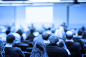 Business conference with lecturer and audience. Shallow DOF, selective focus.