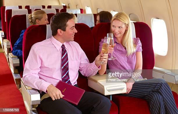 Business couple celebrating on plane