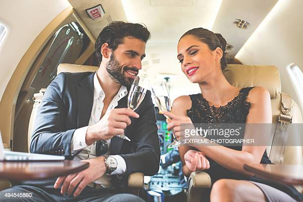 Business couple drinking champagne in private aeroplane