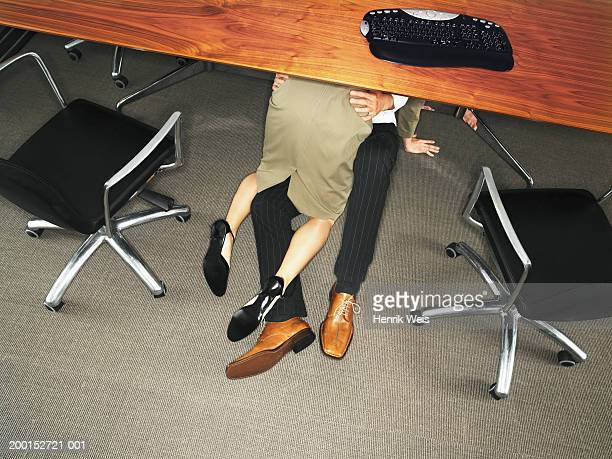Business couple embracing under desk, elevated view