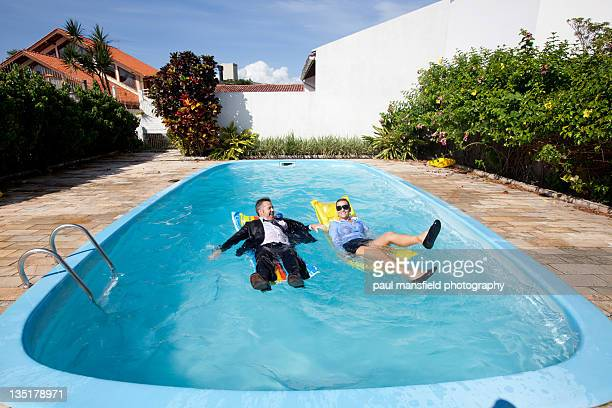 Business couple floating in swimming pool