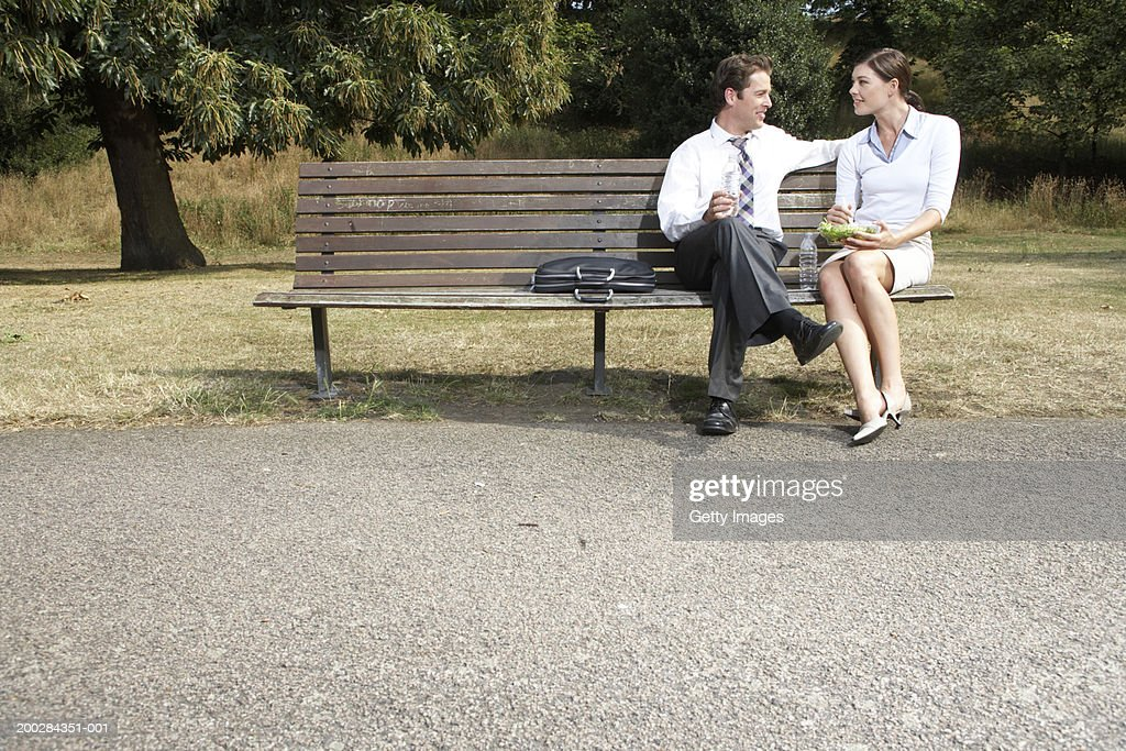 Business couple having lunch on park bench : Stock Photo