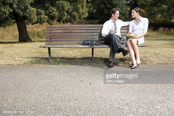 Business couple having lunch on park bench