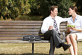 Business couple having lunch on park bench, smiling