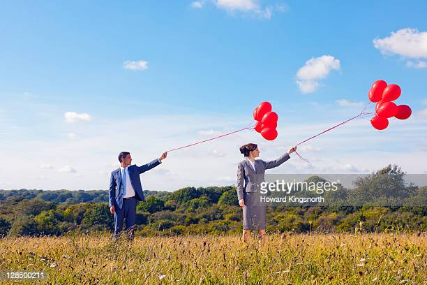 business couple holding bunch of balloons