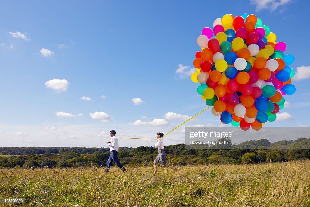 business couple holding bunch of balloons : Stock Photo