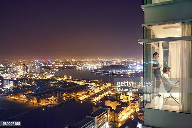 Business couple in city apartment at night