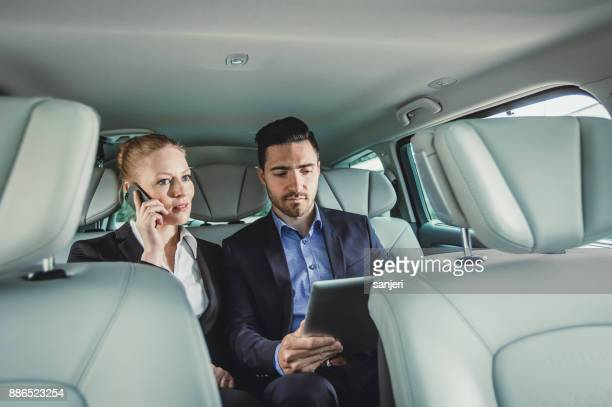 Business Couple in the Car, Using Portable Devices