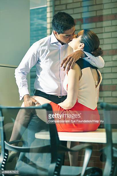 Business couple kissing in office
