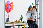Business couple kissing in office with party supplies