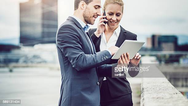Business Couple on Rooftop Planning a Meeting Using Portable Device