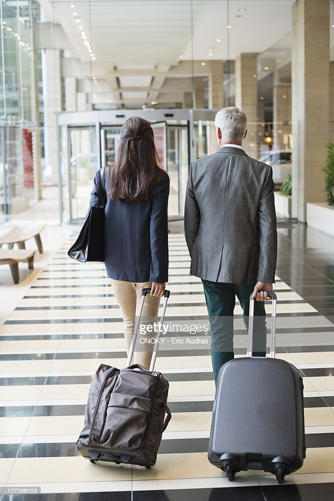 Business couple pulling suitcases in a hotel lobby : Stock Photo