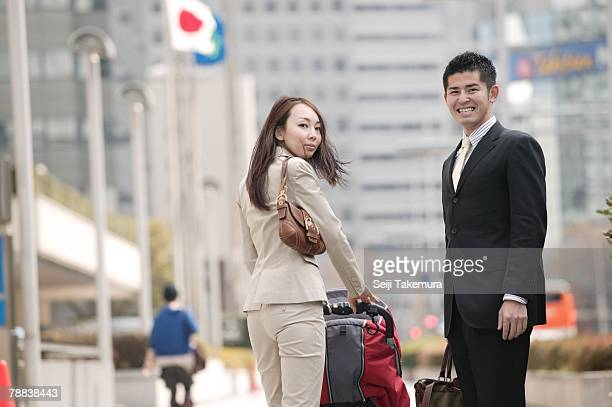 Business couple pushing baby stroller