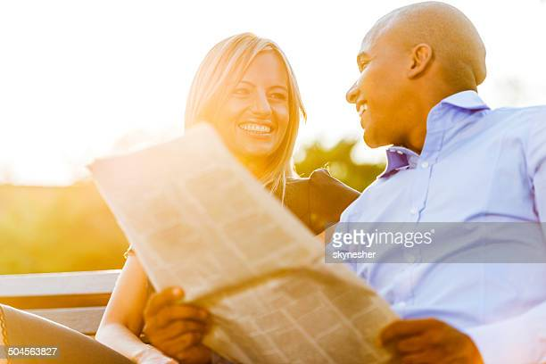 Business-Paar lesen Zeitung bei Sonnenuntergang.