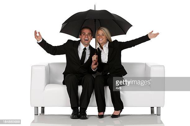 Business couple sitting on a couch under an umbrella