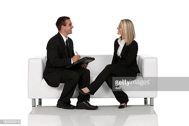 Business-Paar sitzt auf Sofa Gespräch mit anderen