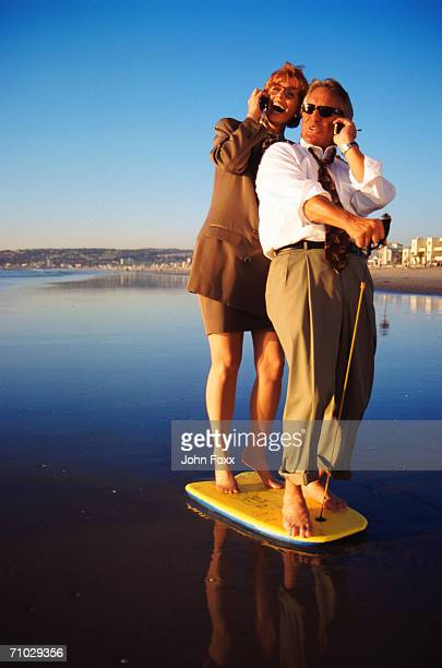 Business couple standing on surfboard, using mobile phone