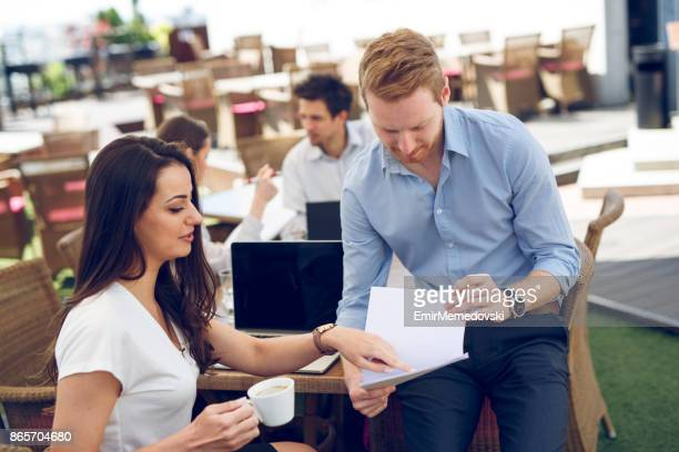 Business couple talking about new work project during coffee break