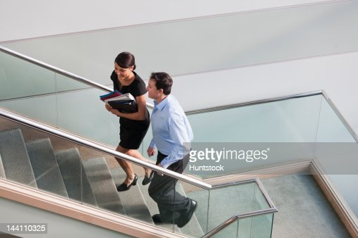 Business couple talking on stairs of office building : Stock Photo