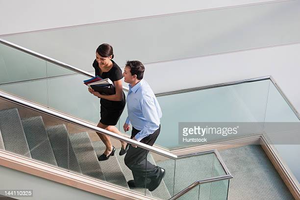 Business couple talking on stairs of office building