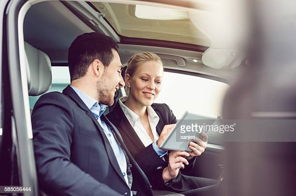 Business Couple using a Tablet in the Car