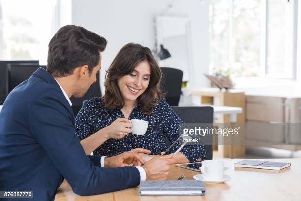 Business couple using digital tablet during lunch meeting