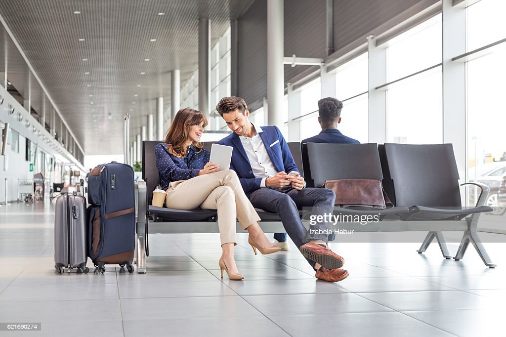 Business couple waiting for flight at airport lounge : Stock Photo