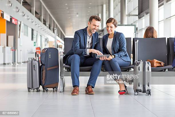 Business couple waiting for flight using digital tablet