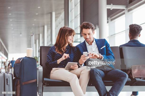 Business couple waiting in airport terminal for flight