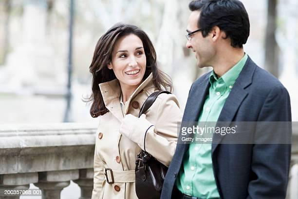 Business couple walking along pavement, smiling, side view