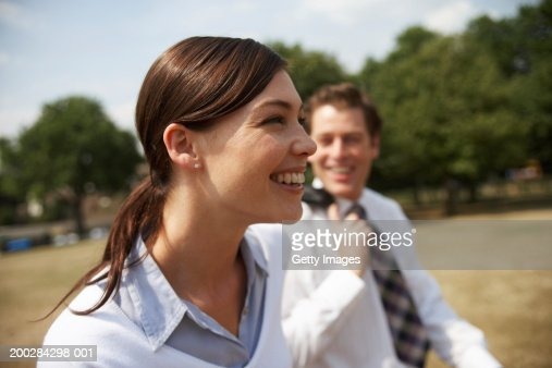 Business couple walking in park, smiling, side view (focus on woman) : Stock Photo