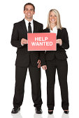 Business couple with Help Wanted Sign board
