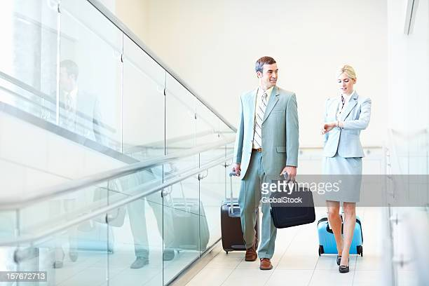 Business couple with travel bags while woman checking out time