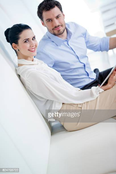 Business co-workers relaxing on sofa using digital tablet
