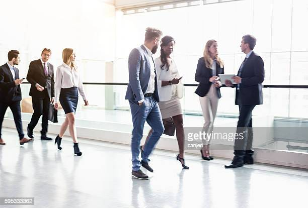 Business coworkers walking along office coridor