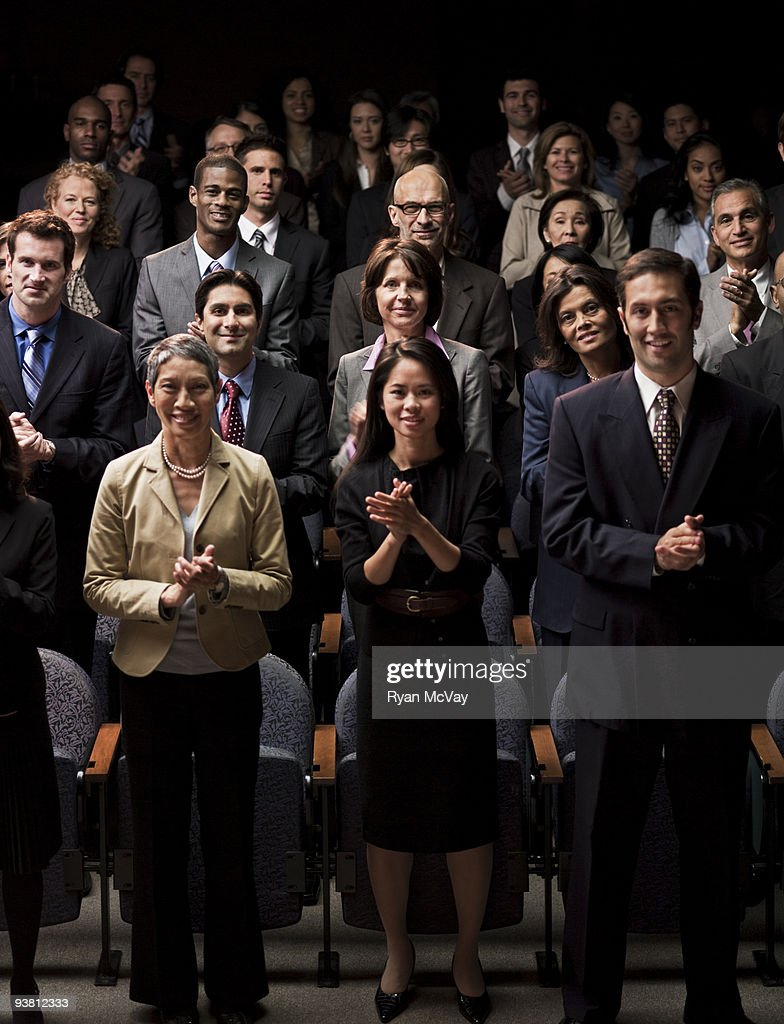 Business crowd clapping in auditorium
