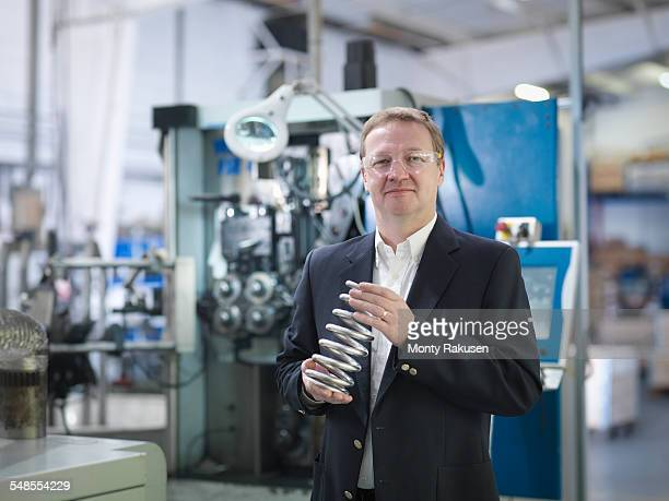 Business director holding spring in automotive factory, portrait