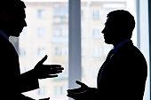 Back lit image of two businessmen arguing