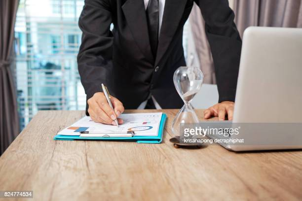 business documents on office table with smart phone and digital tablet and graph financial